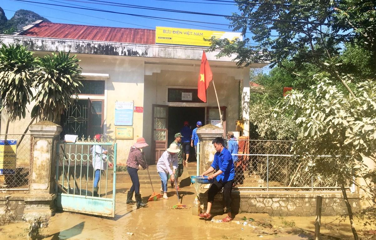 Các đoàn viên thanh niên hỗ trợ lau chùi bùn đất sau mưa lũ tại điểm bưu điện xã Tân Hóa, huyện Minh Hóa, tỉnh Quảng Bình. (Ảnh: Võ Dung/TTXVN)