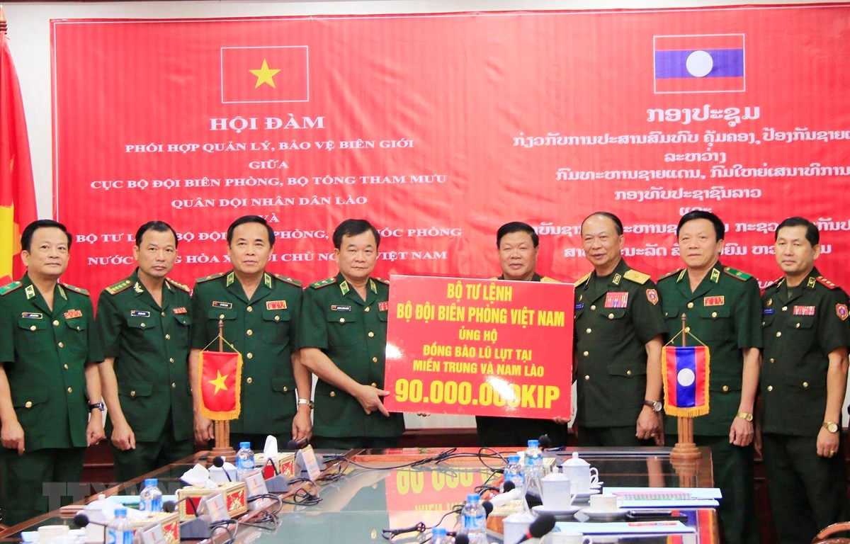Trung tướng Hoàng Xuân Chiến (thứ 5, từ trái sang), Tư lệnh Bộ đội Biên phòng Việt Nam, trao tiền ủng hộ người dân bị thiệt hại tại các tỉnh Trung và Nam Lào cho Bộ Quốc phòng Lào. (Ảnh: Xuân Tú/TTXVN)
