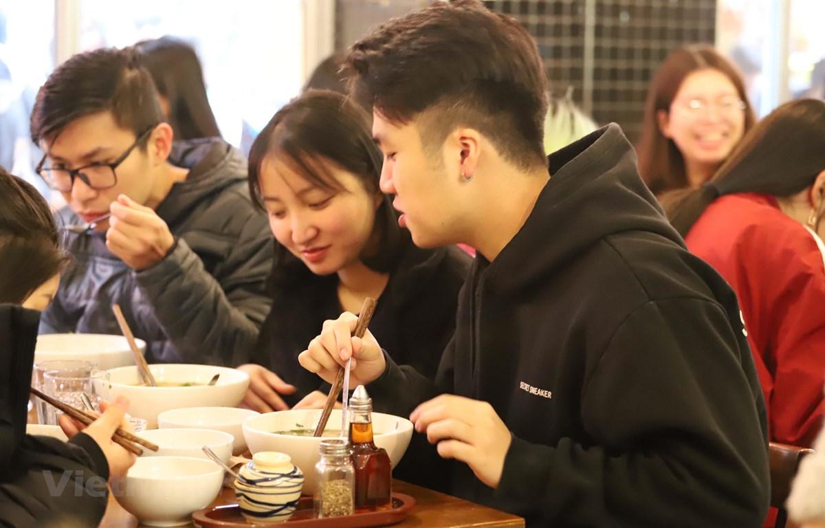 Các bạn trẻ du học sinh Việt Nam tại Melbourne thích thú thưởng thức Phở Thìn 13 Lò Đúc. (Ảnh: Diệu Linh/Vietnam+)