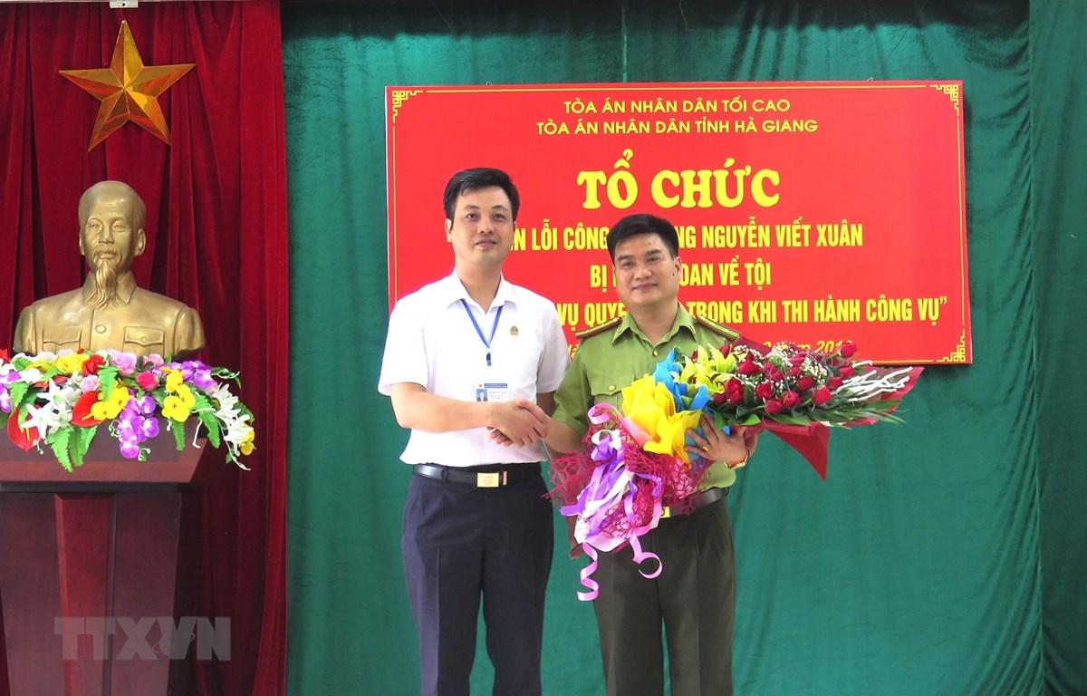 Phó Chánh án TAND tỉnh Hà Giang Trương Huy Huân tặng hoa cho ông Nguyễn Viết Xuân. (Ảnh: Minh Tâm-TTXVN)