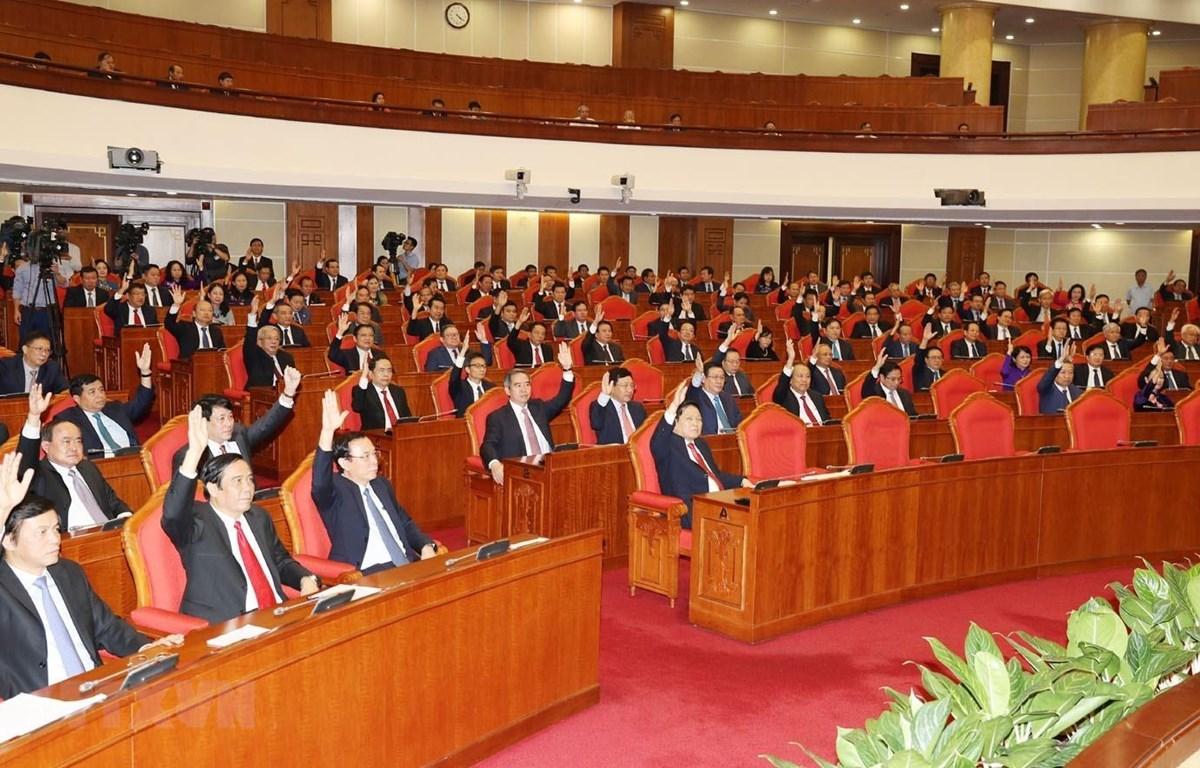 Các đồng chí lãnh đạo Đảng, Nhà nước và các đại biểu biểu quyết thông qua Nghị quyết Hội nghị Trung ương lần thứ mười một. (Ảnh: Trí Dũng/TTXVN)