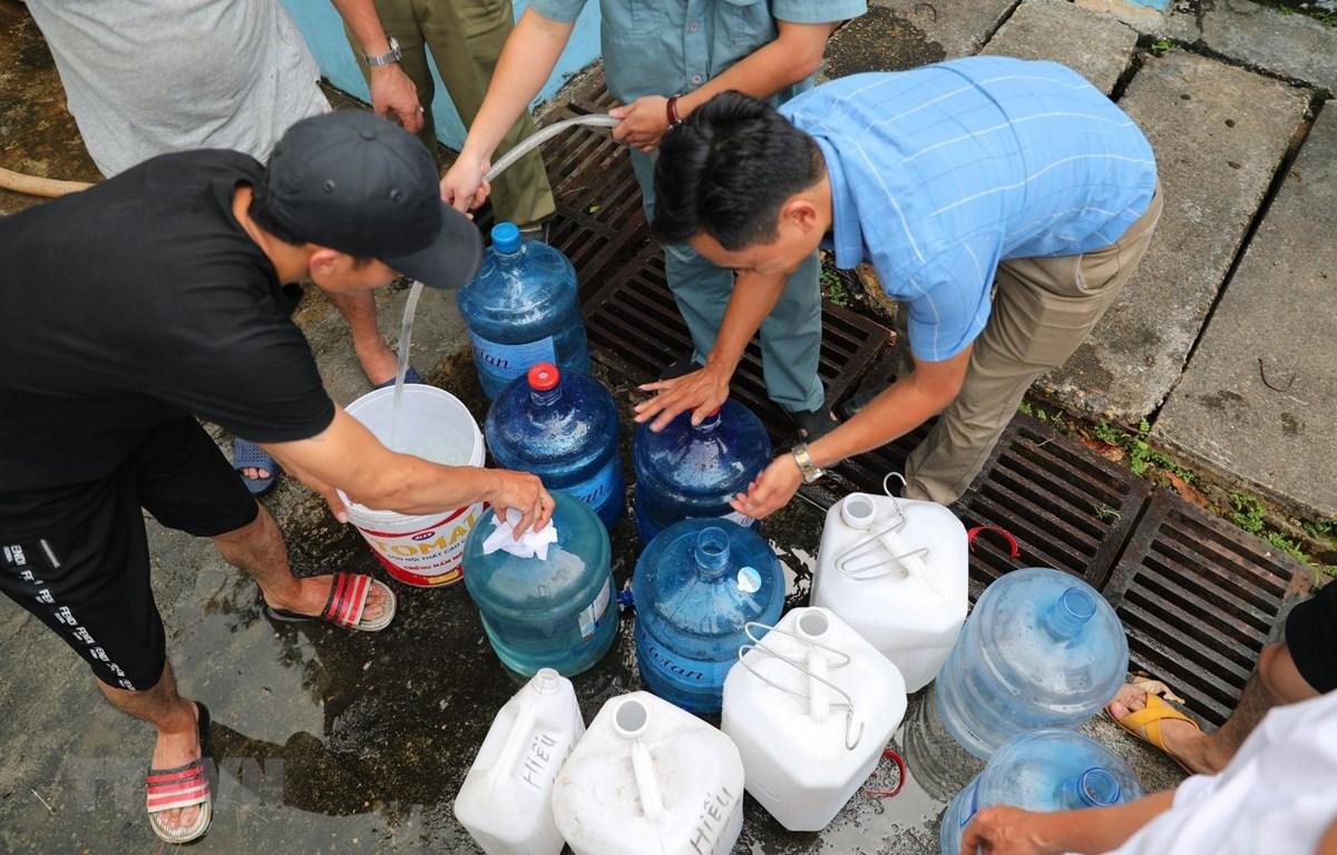 Người dân xếp hàng chờ lấy nước miễn phí tại Nhà máy nước Hạ Đình (địa chỉ, số 14 ngõ 192 phố Hạ Đình). (Ảnh: Thành Đạt/TTXVN)
