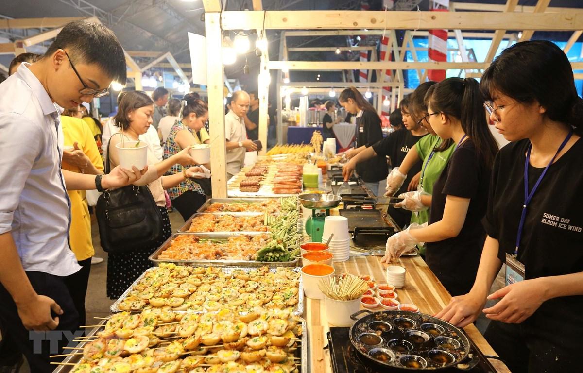 Đông đảo thực khách trong nước và quốc tế thưởng thức món bánh khọt tại liên hoan. (Ảnh: Thanh Vũ/TTXVN)