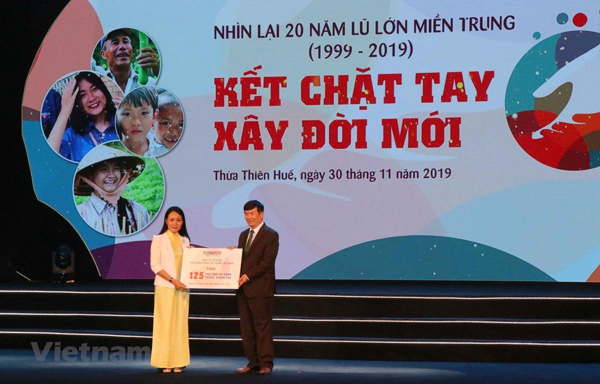 Đại diện nhà tài trợ trao bảng biểu trưng hỗ trợ xây dựng 125 căn nhà cho người dân tỉnh Thừa Thiên- Huế. (Ảnh: Đỗ Trưởng/Vietnam+)