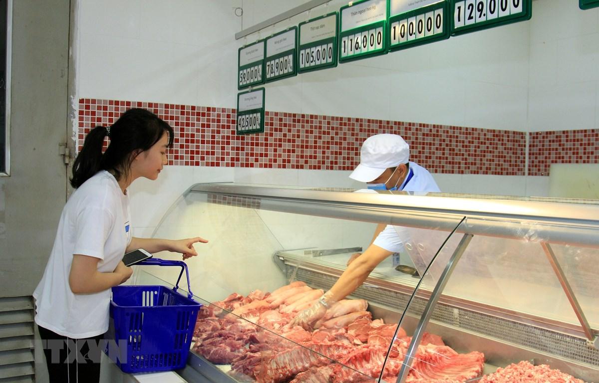 Khách hàng chọn mua thịt lợn tại siêu thị Co.opmart Hà Đông (Hà Nội). (Ảnh: TTXVN)