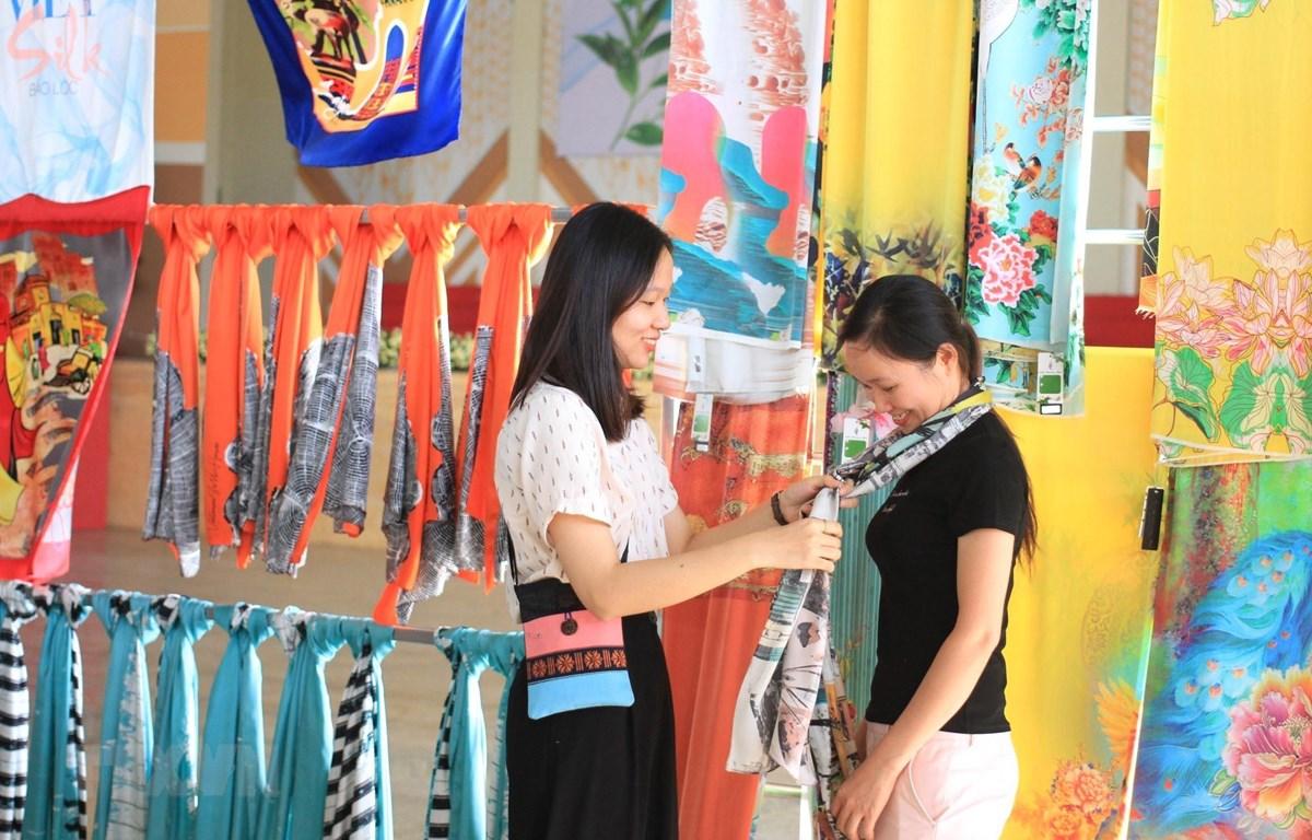 Rất nhiều du khách yêu thích sản phẩm tơ lụa. (Ảnh: Đặng Tuấn/TTXVN)