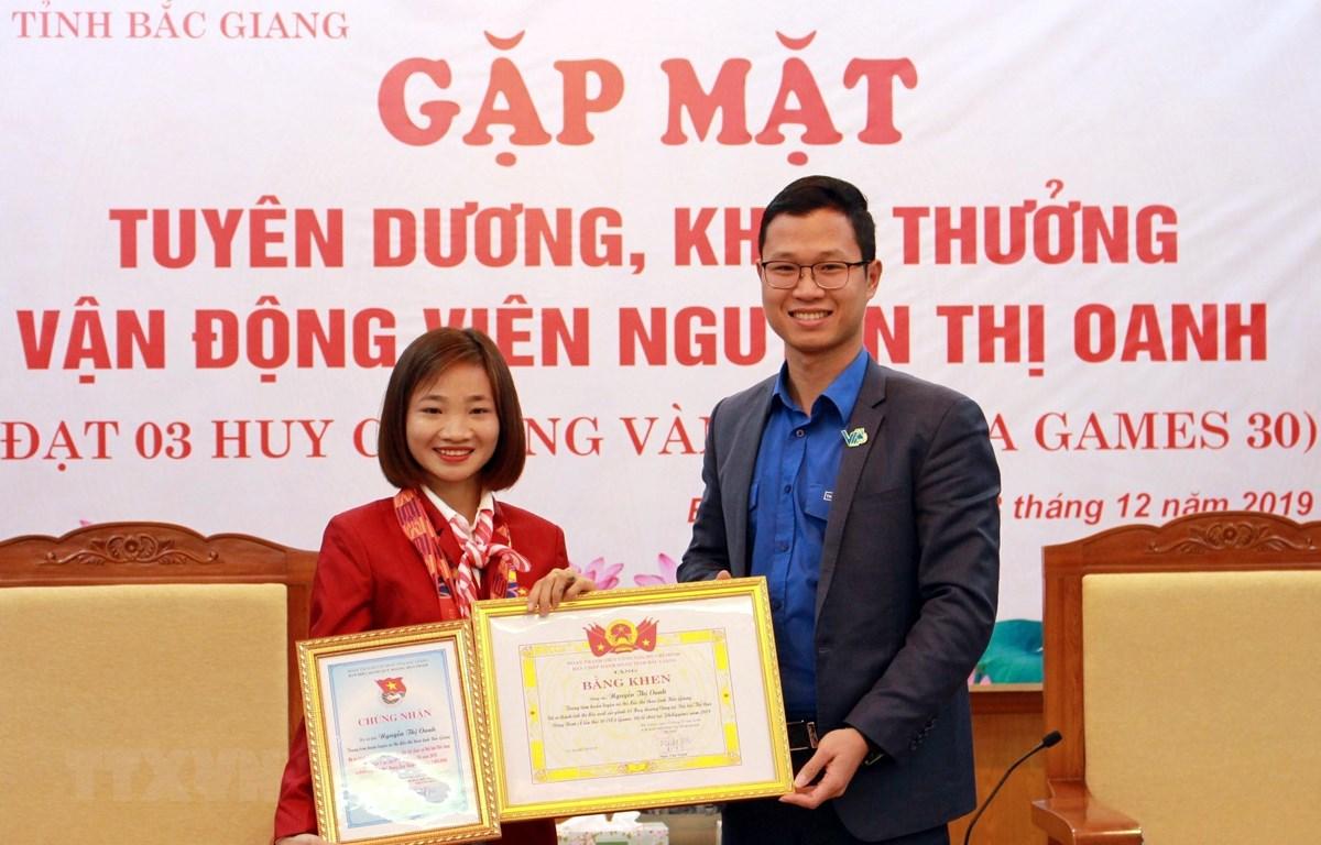 Đại diện Tỉnh đoàn Bắc Giang trao tặng bằng khen cho vận động viên Nguyễn Thị Oanh. (Ảnh: Đồng Thúy/TTXVN)