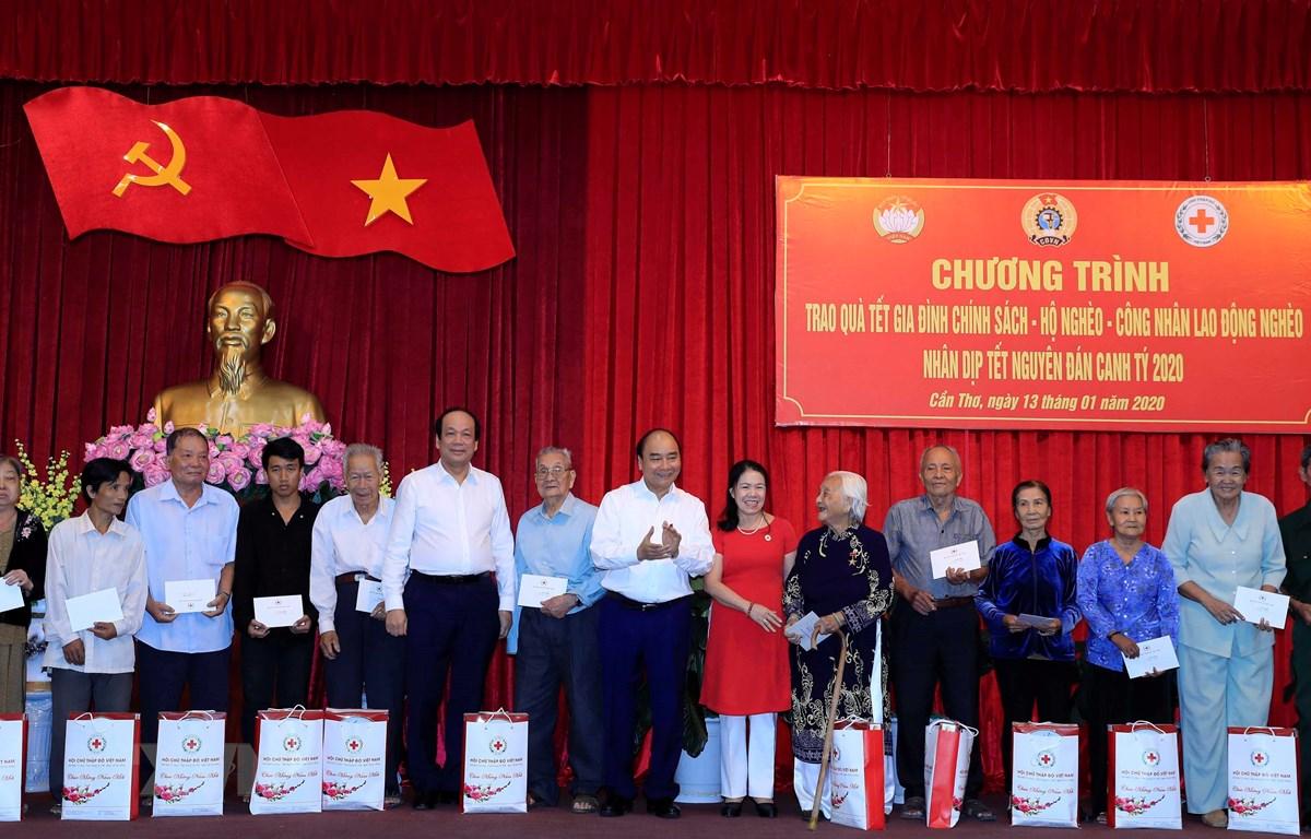 Thủ tướng Nguyễn Xuân Phúc tặng quà gia đình chính sách, hộ nghèo tại thành phố Cần Thơ. (Ảnh: Thống Nhất/TTXVN)