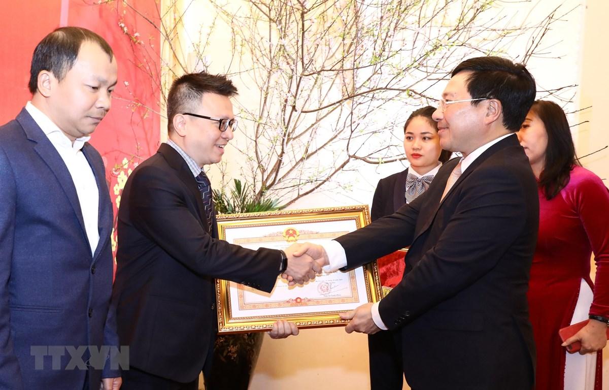 Phó Thủ tướng, Bộ trưởng Bộ Ngoại giao Phạm Bình Minh trao Bằng khen của Thủ tướng Chính phủ tặng Thông tấn xã Việt Nam. (Ảnh: Văn Điệp/TTXVN)