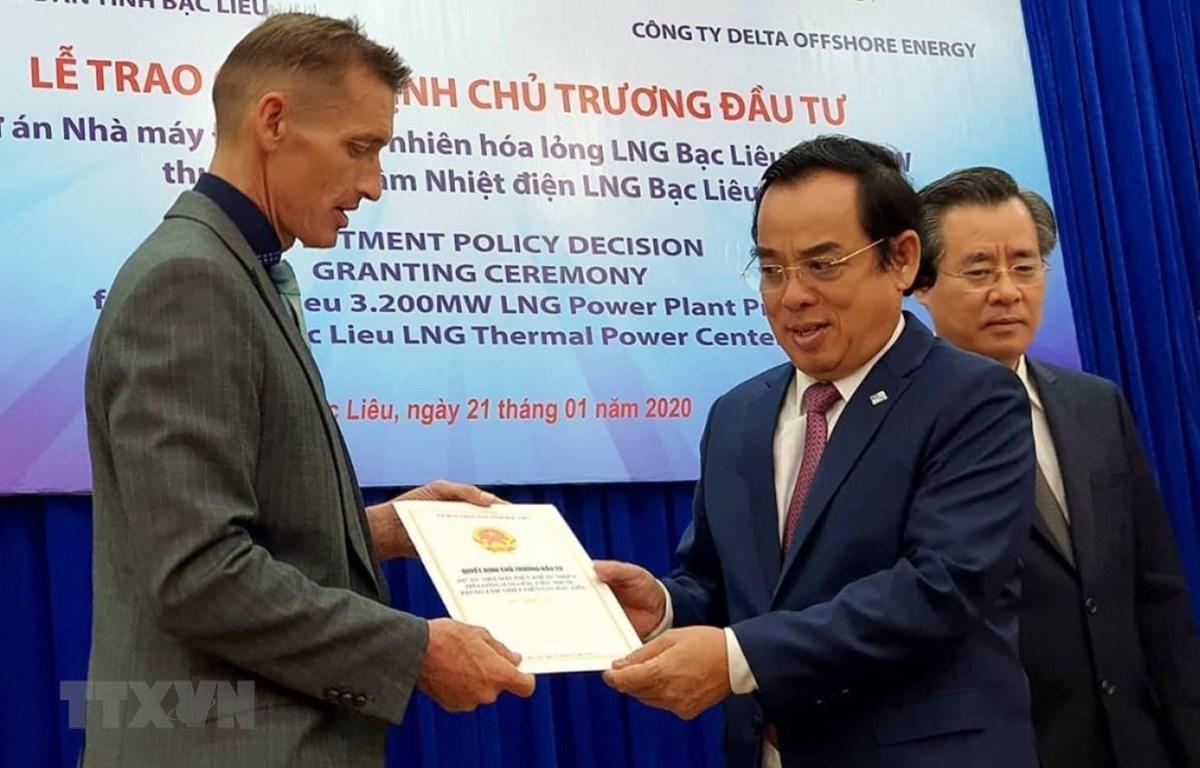 Ông Dương Thành Trung, Chủ tịch UBND tỉnh Bạc Liêu trao quyết định chủ trương đầu tư cho đại diện Công ty TNHH Delta Offshore Energy Pte. Ltd. (Ảnh: Huỳnh Sử/TTXVN)