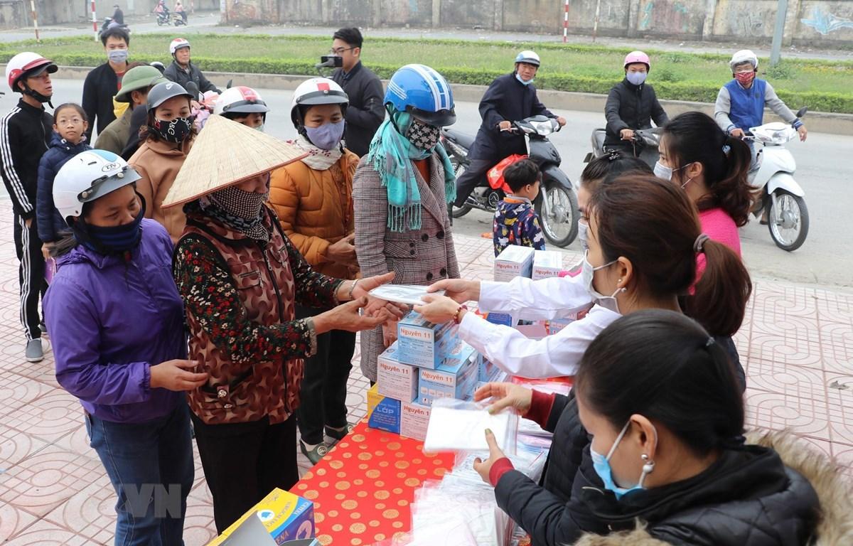 Doanh nghiệp tư nhân Anh Khoa phát khẩu trang miễn phí trên đường Lê Thái Tổ, thành phố Ninh Bình. (Ảnh: Đức Phương/TTXVN)