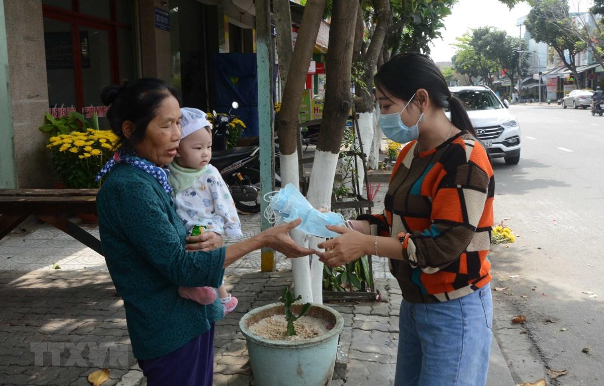 Chủ cửa hàng Bống Tea and Coffe (136C Ông Ích Đường, thành phố Đà Nẵng) phát khẩu trang miễn phí cho khách hàng. (Ảnh: Văn Dũng/ TTXVN)