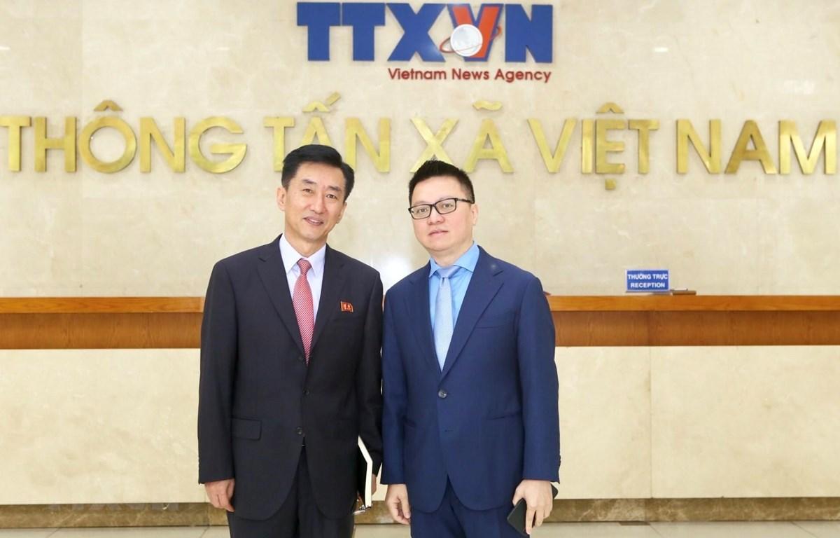 Phó Tổng Giám đốc TTXVN Lê Quốc Minh và ông Ri Ho-jun, Tham tán, Đại biện lâm thời Đại sứ quán Cộng hòa Dân chủ Nhân dân Triều Tiên tại Việt Nam. (Ảnh: Minh Quyết/TTXVN)