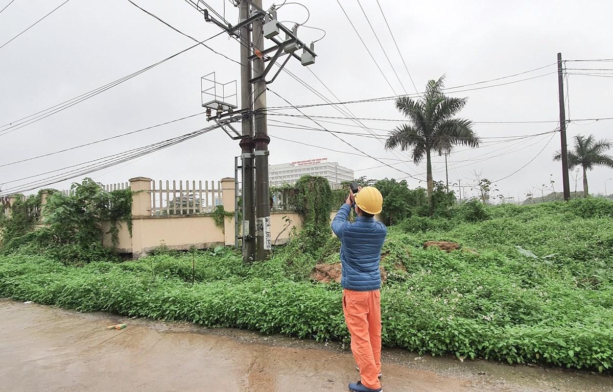 Công nhân Công ty Điện lực Đông anh kiểm tra đo nhiệt tại mối tiếp xúc cấp điện cho Bệnh viện Nhiệt đới Trung ương cơ sở Đông Anh. (Ảnh: Mạnh Khánh/TTXVN)