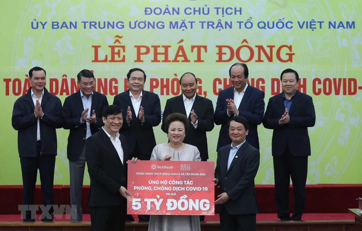 Thủ tướng Nguyễn Xuân Phúc cùng các đại biểu chứng kiến các tổ chức và cá nhân quyên góp ủng hộ công tác phòng, chống dịch COVID-19. (Ảnh: Thống Nhất/TTXVN)