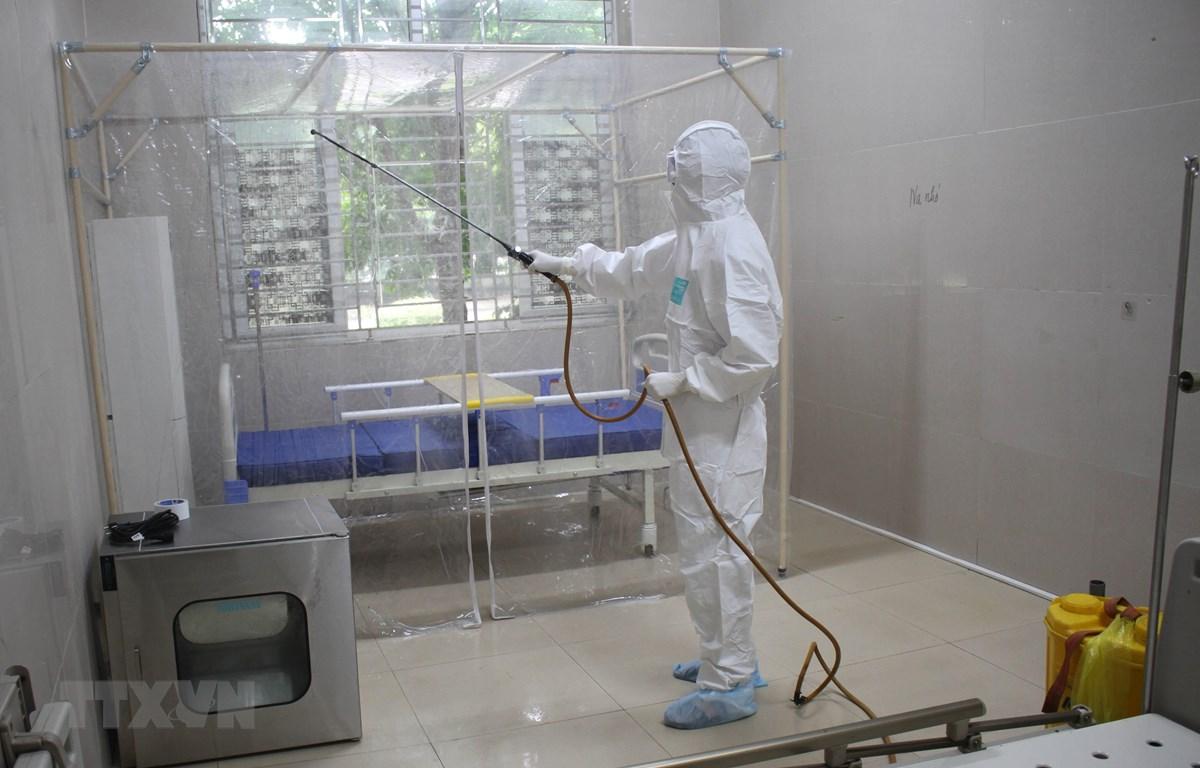 Nhân viên y tế Khu cách ly đặc biệt phun thuốc khử trùng. (Ảnh: Thùy Dung/TTXVN)