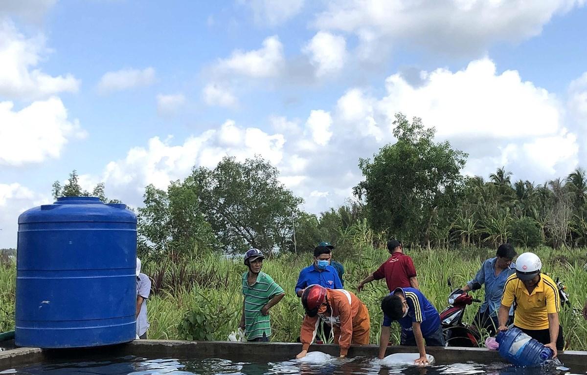 Người dân vùng hạn, mặn xã Thạnh Phú Đông, huyện Giồng Trôm, tỉnh Bến Tre vui mừng nhận nước ngọt được trao tặng. (Ảnh: TTXVN phát)