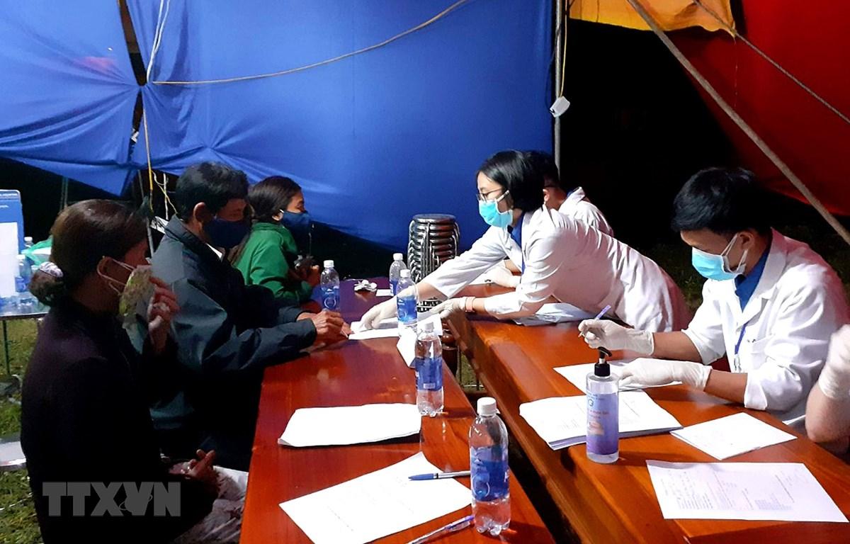 Sinh viên tình nguyện hướng dẫn người dân khai báo y tế tại chốt kiểm soát y tế thị xã Hương Trà. (Ảnh: Tường Vi/TTXVN)