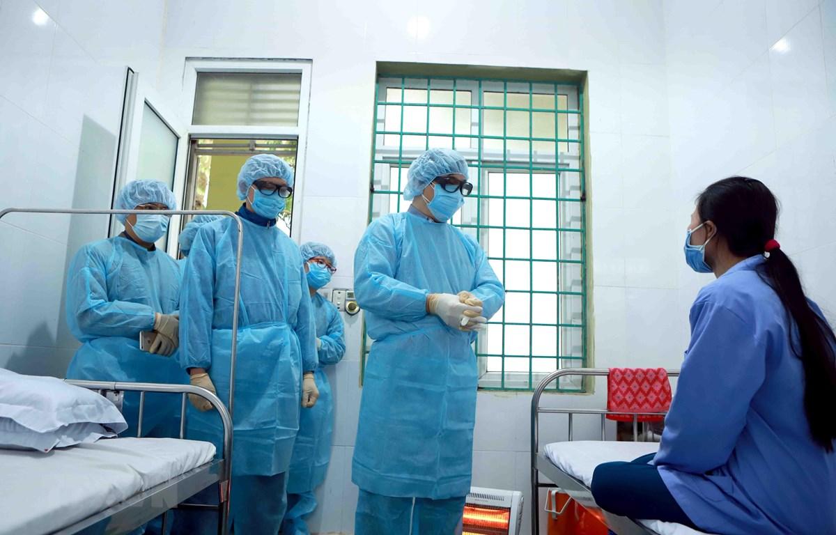 Đội cơ động phản ứng nhanh chống dịch viêm đường hô hấp (Bộ Y tế) thăm hỏi nữ bệnh nhân dương tính với virus corona tại Trung tâm Y tế huyện Bình Xuyên (Vĩnh Phúc). (Ảnh: Hoàng Hùng/TTXVN)