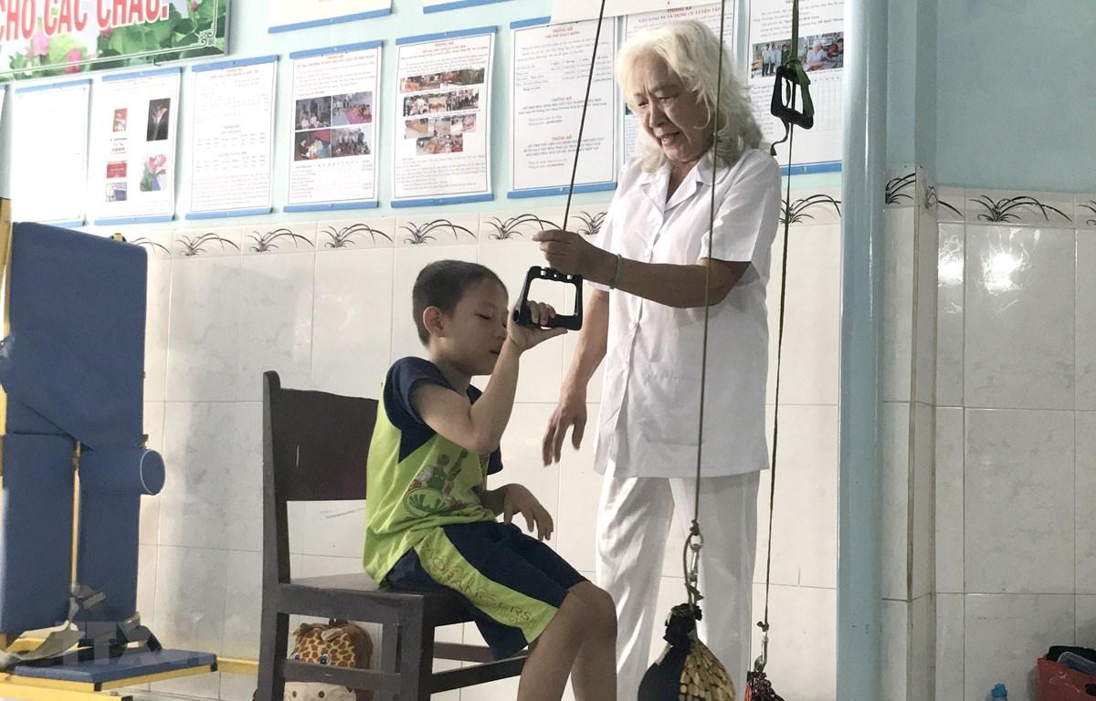 Bà Nguyễn Ngọc Điểu tập luyện phục hồi chức năng vận động cho bé Phan Thanh Phong. (Ảnh: Lê Thúy Hằng/TTXVN)
