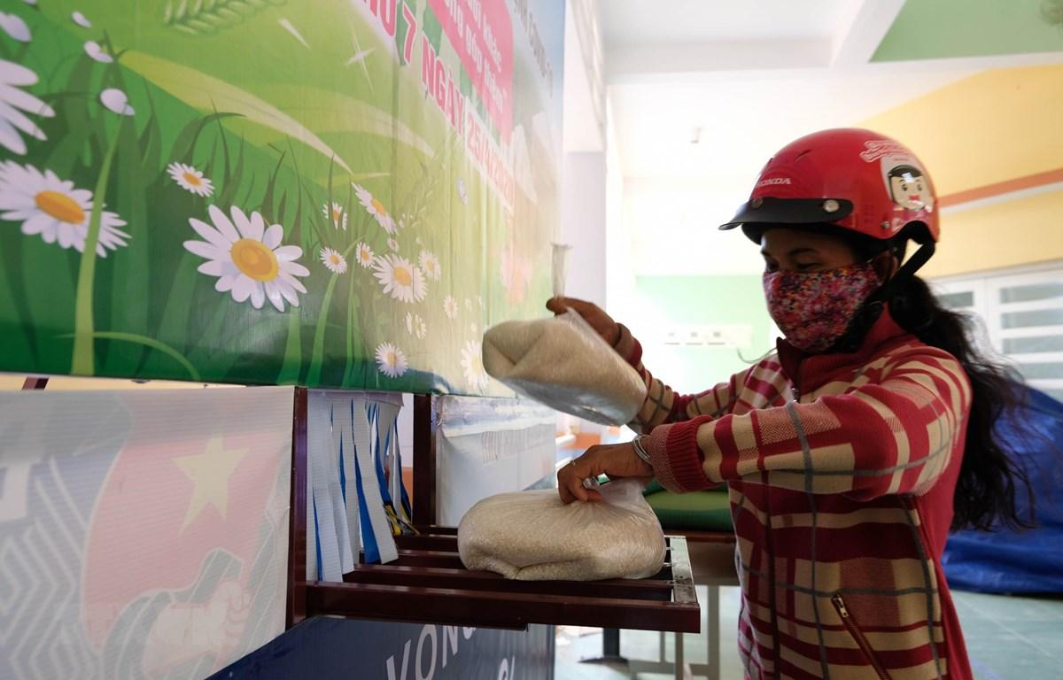 Người dân nhận gạo từ 'ATM gạo' tại thị trấn Khánh Vĩnh (huyện Khánh Vĩnh, Khánh Hoà) trong ngày 25/4. (Ảnh: Nguyễn Dũng/TTXVN)