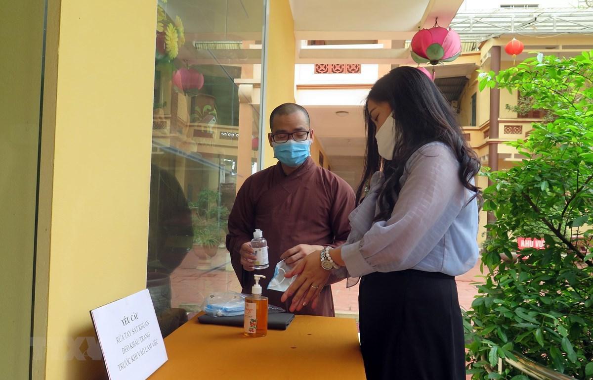 Sư thầy chùa Anh Vinh (thành phố Tuyên Quang) hướng dẫn người dân thực hiện rửa tay trước khi vào lễ chùa. (Ảnh Quang Đán/TTXVN)