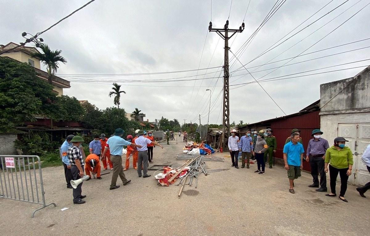 Lực lượng chức năng tháo dỡ lều bạt, băng rôn, khẩu hiệu dựng trái phép trên hành lang giao thông ở khu vực xã An Phượng. (Ảnh: Mạnh Tú/TTXVN)