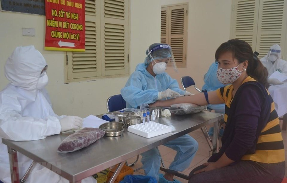 Lấy mẫu xét nghiệm nhanh virus SARS-CoV-2 cho tiểu thương chợ đầu mối. (Ảnh: TTXVN/phát)