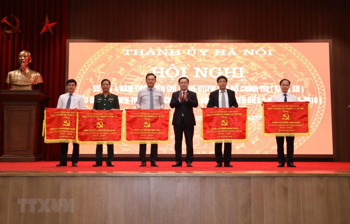 Bí thư Thành ủy Hà Nội Vương Đình Huệ trao tặng Cờ thi đua của Ban Thường vụ Thành ủy Hà Nội cho các Đảng bộ đạt thành tích xuất sắc trong nhiệm kỳ 2015/2019. (Ảnh: Văn Điệp/TTXVN)
