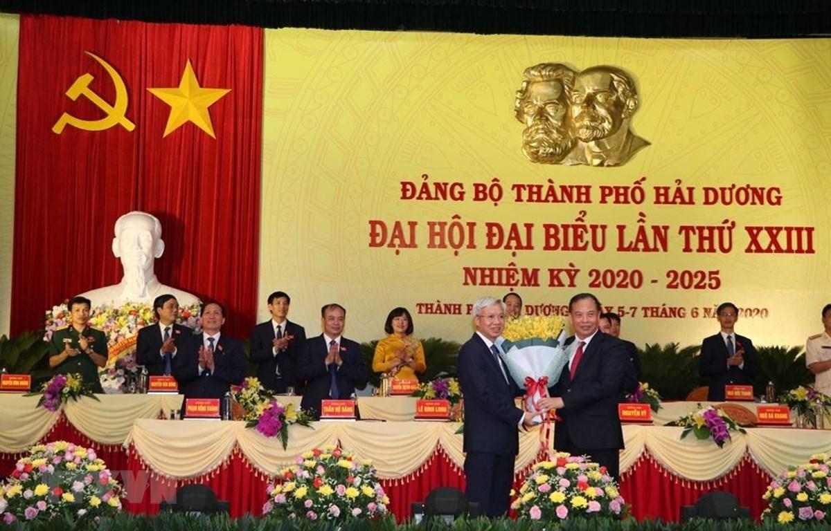 Ủy viên Trung ương Đảng, Bí thư Tỉnh ủy Hải Dương Nguyễn Mạnh Hiển tặng hoa chúc mừng tân Bí thư Thành ủy Hải Dương khóa XXIII nhiệm kỳ 2020–2025 Lê Đình Long. (Ảnh: Mạnh Minh/TTXVN)
