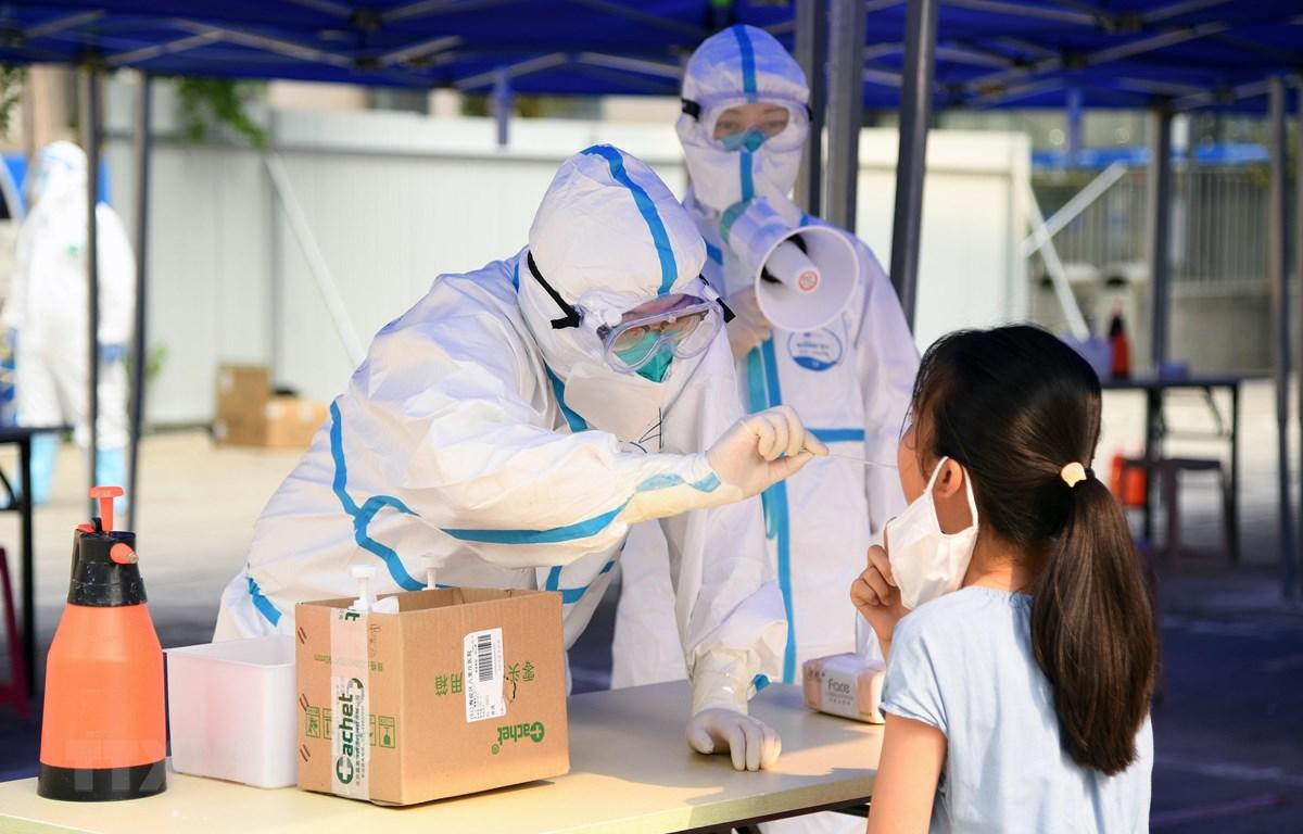 Nhân viên y tế lấy mẫu xét nghiệm COVID-19 cho người dân tại Bắc Kinh, Trung Quốc ngày 23/6/2020. (Ảnh: THX/TTXVN)