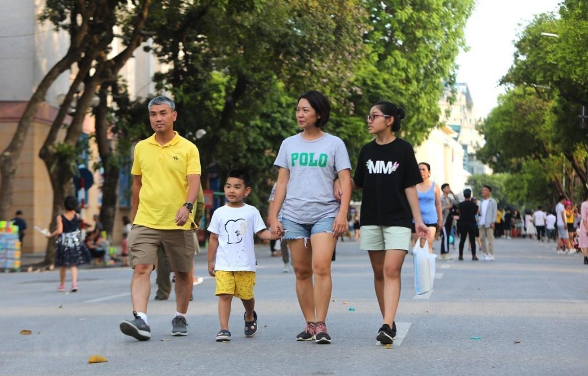 Nhiều gia đình đưa các em nhỏ đi chơi trên phố đi bộ nhân ngày Quốc tế thiếu nhi. (Ảnh: Thành Đạt/TTXVN)