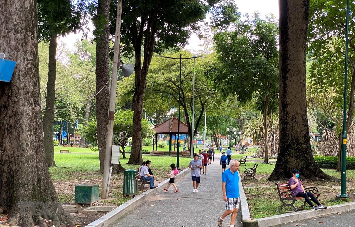 Tại những khu vực không có rào chắn trong công viên Tao Đàn, người dân vẫn tập trung thành từng nhóm nhỏ để tập thể thao, không ít người vi phạm quy định về đeo khẩu trang và giữ khoảng cách an toàn. (Ảnh: Hồng Giang/TTXVN)