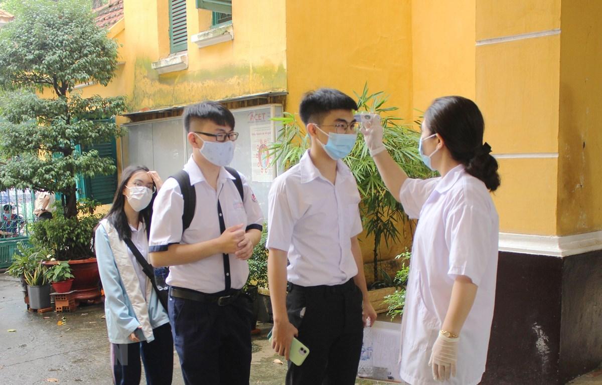 Hơn 75.000 thí sinh Thành phố Hồ Chí Minh đến làm thủ tục dự thi tốt nghiệp THPT đều được đo kiểm tra thân nhiệt. (Ảnh: Xuân Anh/TTXVN)