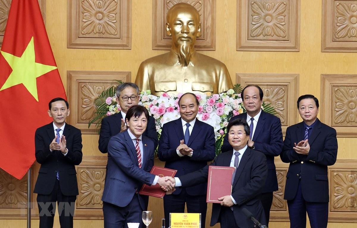 Thủ tướng Nguyễn Xuân Phúc chứng kiến lễ trao thoả thuận hợp tác giữa Cục Đầu tư nước ngoài (Bộ Kế hoạch và Đầu tư) và Tổ chức Xúc tiến Thương mại Nhật Bản. (Ảnh: Thống Nhất/TTXVN)