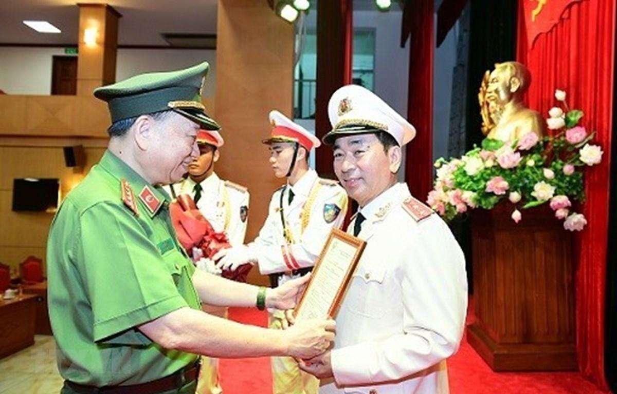 Bộ trưởng Bộ Công an Tô Lâm trao Quyết định của Chủ tịch nước thăng cấp bậc hàm từ Thiếu tướng lên Trung tướng đối với đồng chí Trần Quốc Tỏ, Thứ trưởng Bộ Công an. (Ảnh: TTXVN phát)