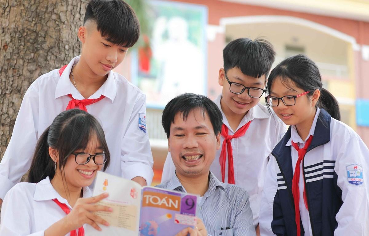 Thầy giáo Nguyễn Đức Trường và các học sinh trường THCS Đa Tốn, huyện Gia Lâm (Hà Nội). (Ảnh: Thanh Tùng/TTXVN)