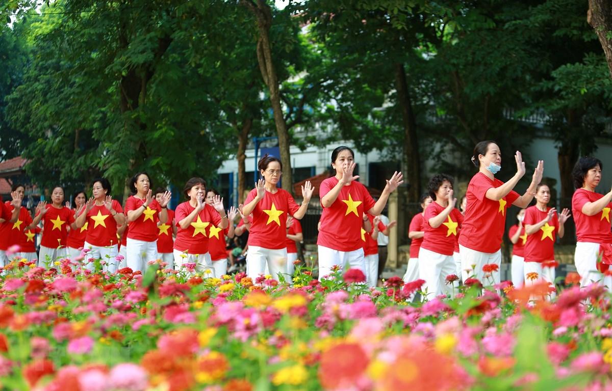 Người dân Thủ đô mặc đồng phục cờ Tổ quốc biểu diễn bài tập dưỡng sinh bên hồ Gươm sáng 2/9. (Ảnh: TTXVN)