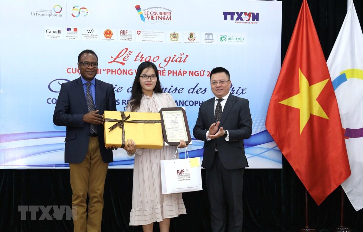 Phó Tổng giám đốc TTXVN Lê Quốc Minh và Trưởng đại diện khu vực châu Á-Thái Bình Dương của Tổ chức quốc tế Pháp ngữ OIF Chékou Oussouman trao giải Nhất cho tác giả Man Khánh Ly. (Ảnh: Hoàng Hiếu/TTXVN)