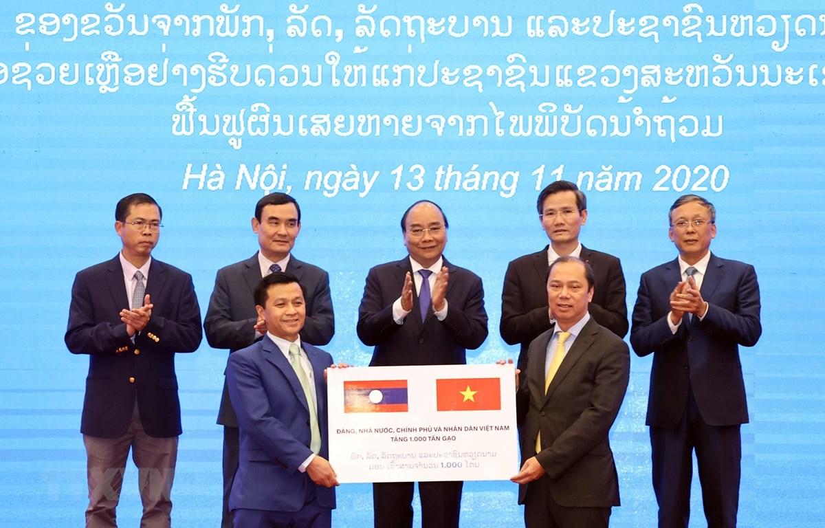 Thứ trưởng Bộ Ngoại giao Nguyễn Quốc Dũng (bên phải) trao tượng trưng 1.000 tấn gạo cho đại diện Đại sứ quán Lào tại Việt Nam trước sự chứng kiến của Thủ tướng Nguyễn Xuân Phúc. (Ảnh: Thống Nhất/TTXVN)