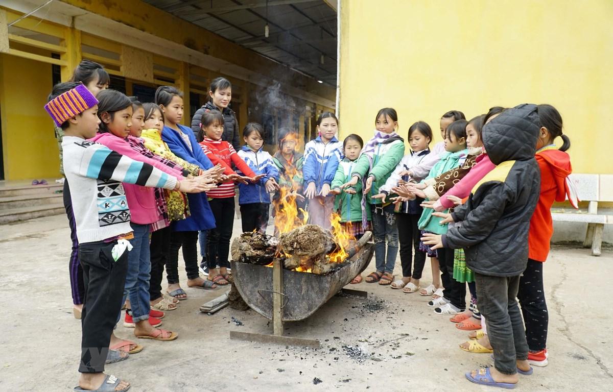 Cô và trò Trường Phổ thông Dân tộc Bán trú Tiểu học Leng Su Sìn (huyện Mường Nhé, Điện Biên) đốt lửa sưởi ấm. (Ảnh: Xuân Tư/TTXVN)