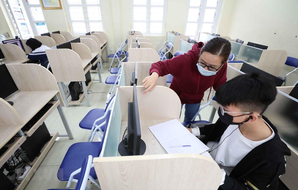 Học sinh trường THCS Thăng Long (Ba Đình, Hà Nội) không có điều kiện học trực tuyến tại nhà được nhà trường bố trí và phân công giáo viên giúp đỡ học tại phòng máy của trường. (Ảnh: Thanh Tùng/TTXVN)