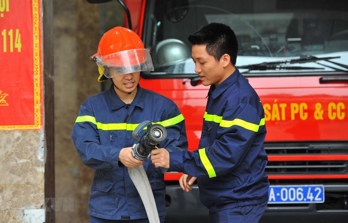 Trung úy Vũ Ngọc Hoàng (phải) hướng dẫn nghiệp vụ cho chiến sỹ mới tại đơn vị. (Ảnh: Minh Đức/TTXVN)