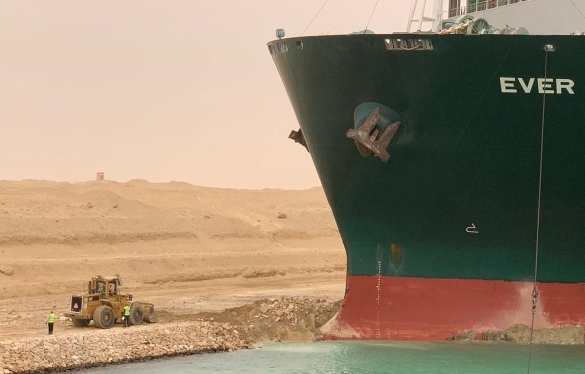 Chiếc máy xúc đứng cạnh siêu tàu chở hàng Ever Given mắc cạn tại Kênh đào Suez, Ai Cập, ngày 24/3. (Ảnh: THX/ TTXVN)