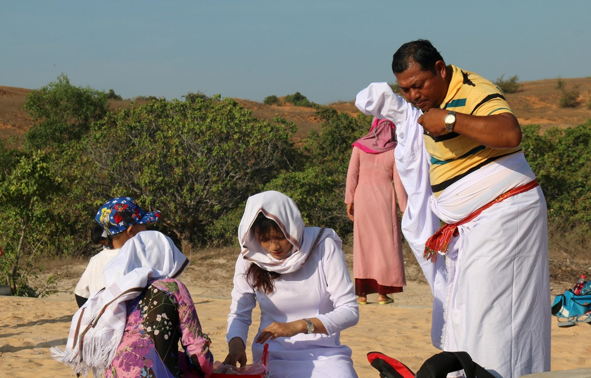 Chuẩn bị đồ cúng và mặc đồ truyền thống để thực hiện Lễ tảo mộ. (Ảnh: Nguyễn Thanh/TTXVN)