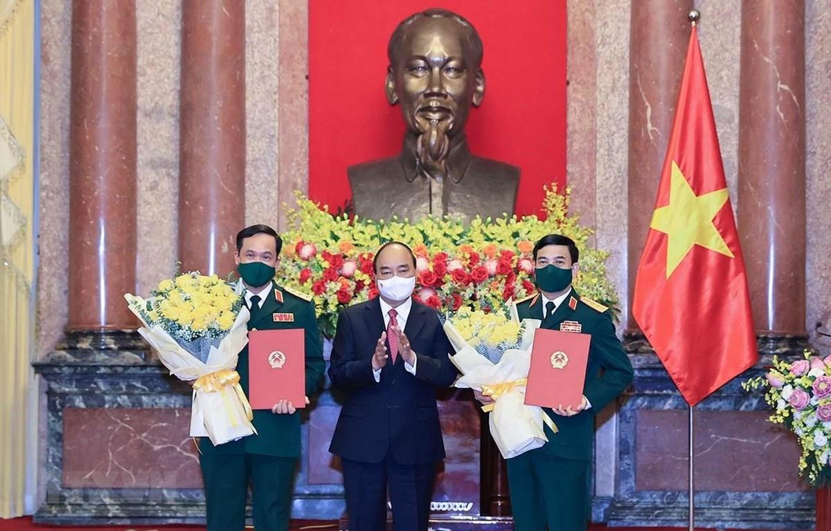 Chủ tịch nước Nguyễn Xuân Phúc trao Quyết định thăng quân hàm cho Bộ trưởng Bộ Quốc phòng Phan Văn Giang và Thứ trưởng Bộ Quốc phòng Vũ Hải Sản. (Ảnh: Thống Nhất/TTXVN)
