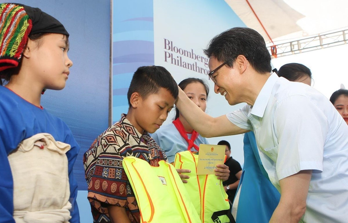 Phó Thủ tướng Chính phủ Vũ Đức Đam tặng áo phao cho các em nhỏ tại buổi lễ. (Ảnh: Thanh Tùng/TTXVN)