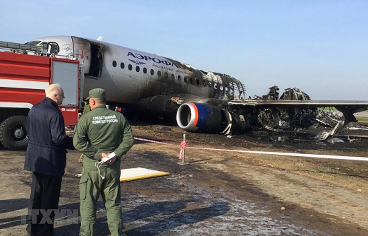 Lực lượng chức năng điều tra tại hiện trường máy bay Sukhoi Superjet 100 của Aeroflot bị phá hủy sau vụ cháy. (Ảnh: AFP/TTXVN)