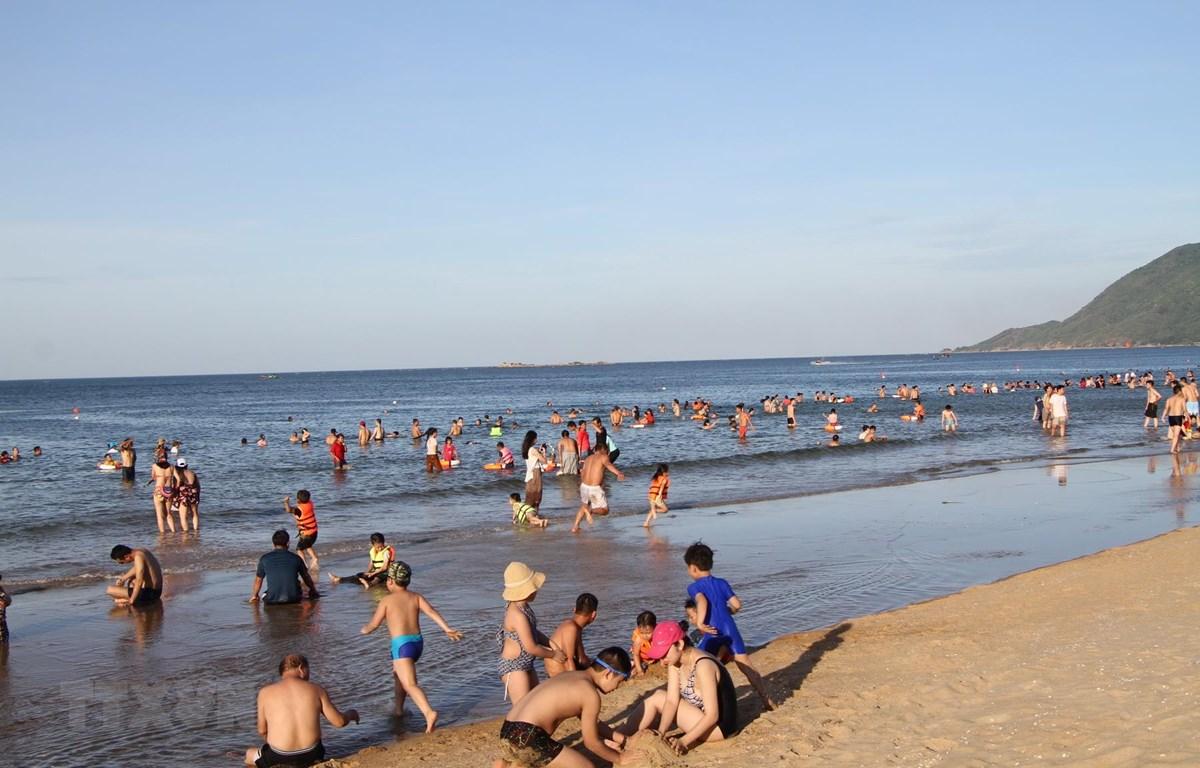 Bãi biển Thiên Cầm hút hút lượng lớn người lớn và trẻ em ra tắm tránh nắng nóng. (Ảnh: Phan Quân/TTXVN)
