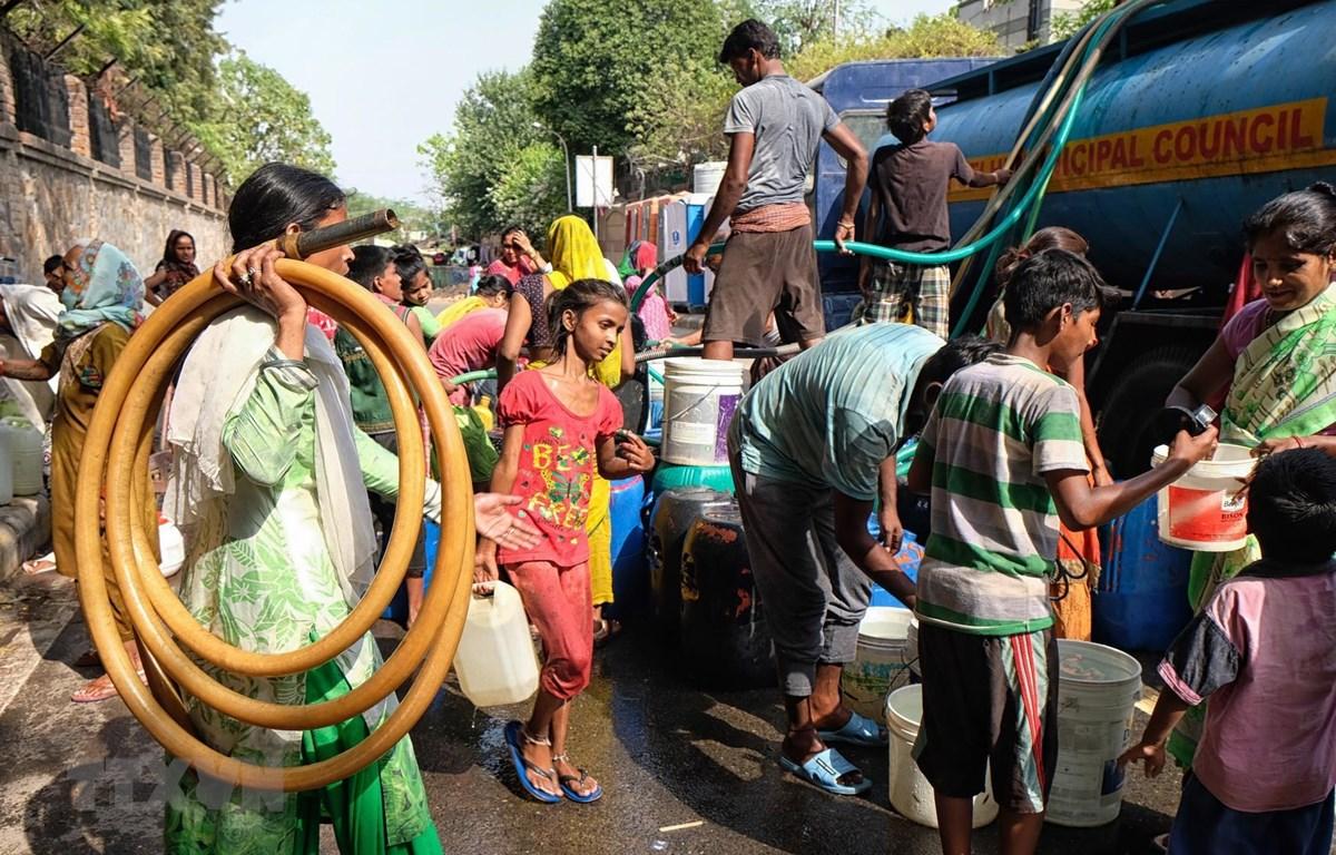 Người dân chờ lấy nước trong thời tiết nắng nóng tại khu vực Sanjay, New Delhi, Ấn Độ. (Ảnh: AFP/ TTXVN)